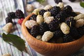 picture of mulberry  - Ripe white and black mulberries in a wooden bowl on the table close - JPG