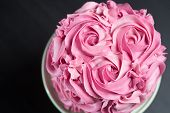 image of icing  - Overhead view of a freshly baked cake decorated with pink icing sugar roses displayed on a cake stand over a black background with copyspace - JPG