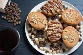 picture of hazelnut  - Freshly baled hazelnut and coffee cakes decorated with icing sugar and nuts served on a plate with nuts and coffee beans overhead view - JPG