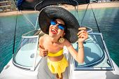pic of top-hat  - Young playful woman with big hat and sunglasses having fun on the yacht - JPG