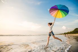 stock photo of sunbathers  - Cheerful caucasian young woman with rainbow umbrella having fun on the Jimbaran beach on Bali before sunset with beautiful ocean and blue sky on background - JPG