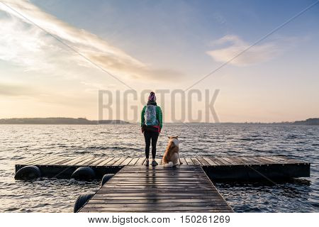 poster of Woman with dog enjoy sunrise and lake relaxing on bridge. Hiker or tourist looking at beautiful morning view with dog friend inspirational landscape on beach. Peaceful people and serene concept.