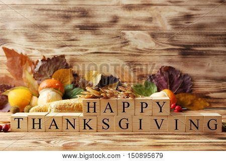 Autumn composition of vegetables, leaves and cubes with inscription HAPPY THANKSGIVING on wooden bac