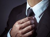 Closeup photo of a man wearing stylish black suit and tie over dark background, body part, mens fas poster