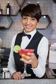 Portrait of smiling bartender holding glass of cocktail in bar counter at bar poster