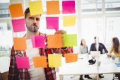 Photo editor looking at multi colored sticky notes on glass in meeting room at creative office poster