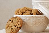 Freshly baked, chocolate chip cookies in a vintage dish with matching cookie jar in the background.