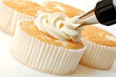Creamy vanilla frosting being swirled onto individual sized angel food cakes with professional pastr
