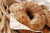 Whole grain wheat bagel in basket with wheat spikes and oats.  Macro with shallow dof.