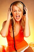 Sexy blond girl with black headphones close up on orange background and fur