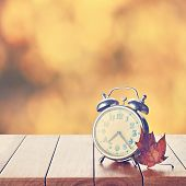 Постер, плакат: Vintage Alarm Clock On Autumn Season Background