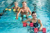 Happy active fitness mature man and senior woman doing exercise with aqua dumbbell in a swimming poo poster