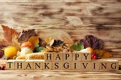 Autumn composition of vegetables, leaves and cubes with inscription HAPPY THANKSGIVING on wooden bac poster