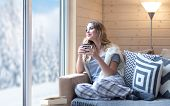 Young beautiful blonde woman with cup of coffee sitting home in living room by the window. Winter sn poster