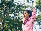 Asian Young Woman Warm Up The Body Stretching Before Morning Exercise And Yoga In The Park Under War poster