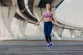 Sportive Woman With Cheerful Expression Does Cardio Training With Jumping Rope, Dressed In Sportswea poster