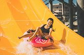 Pretty Smiling Woman On The Rubber Ring Having Fun On The Orange Water Slide In The Aqua Park. Summe poster