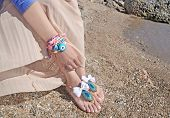 Woman Advertises Traditional Greek Sandals And Jewelry On Beach poster