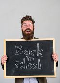 School And Teacher Wait For You. Teacher Or Bearded Educator Stands And Holds Blackboard With Inscri poster