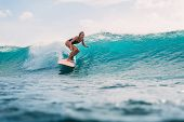 Surf Woman On Surfboard During Surfing. Surfer And Ocean Wave poster
