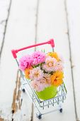 A Beautiful Bouquet Moss Rose Flowers In A Mini Green Bucket In Mini Shopping Cart On Wooden Floor. poster