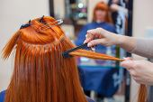 The Hairdresser Does Hair Extensions To A Young, Red-haired Girl, In A Beauty Salon. Professional Ha poster