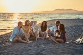 Group of smiling friends with guitar at beach. friends relaxing on sand at beach with guitar and sin poster