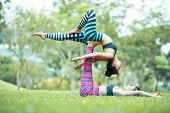 Side View Of Young Asian Women Practicing Acroyoga In Park, Female Base Lying On Grass With Raised U poster