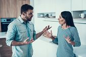 Young Couple Have Disagreement In Kitchen At Home. Quarrel In Young Family. Sad Woman. Divorce Conce poster
