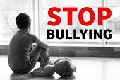 Text STOP BULLYING and sad little boy sitting on floor indoors, black and white effect poster