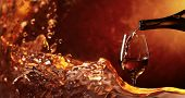 Conceptual Image On The Theme Of Winemaking. Wine Being Pouring Into A Glass. Closeup Wine Splashing poster