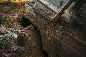 Fragment Of Car Stuck In Dirt, Close Up. Offroad Tire Covered With Mud On Nature Background. Dangero poster