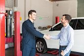 Satisfied Customer Shaking Hands With Car Mechanic At Auto Repair Shop poster