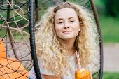 Confident Beautiful Female With Light Curly Hair, Drinks Summer Cocktail, Sits On Hanging Chair, Enj poster