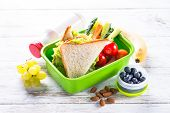 School Lunch Box With Sandwich, Vegetables, Banana, Water, Yogurt, Nuts And Berries On White Wooden  poster