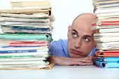 Bald office worker swamped with work
