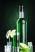 pic of absinthe  - bottle and glasses of absinthe with lime and ice on green background - JPG