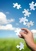stock photo of puzzle  - A hand catching falling puzzle pieces - JPG