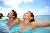 stock photo of infinity pool  - Couple relaxing in swimming pool - JPG