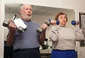 stock photo of mature men  - Senior Adult Couple Working Out in the Gym - JPG