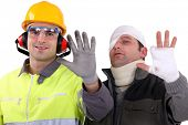 stock photo of neck brace  - Injured tradesman comparing his hand to a healthy colleague - JPG