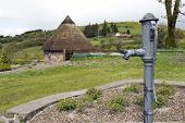 stock photo of mud-hut  - water pump and celtic thatched hut in the Irish countryside - JPG