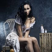 stock photo of nymph  - Sad Sexy Woman Sittind on Chair With Candles - JPG
