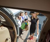 Full length portrait of rich woman with shopping bags boarding private jet while pilot and airhostes