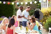stock photo of grill  - Group Of Friends Having Outdoor Barbeque At Home - JPG