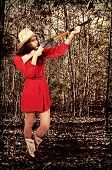 foto of redneck  - Beautiful young country girl woman wearing a stylish cowboy hat shooting a rifle - JPG
