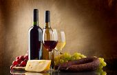 stock photo of sausage  - Wine in bottles and glasses grapes cheese an sausage on linen background - JPG