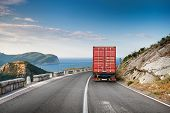 pic of travel trailer  - Cargo truck on the mountain highway with blue sky and sea on a background - JPG
