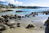 Beautiful beach cove in Laguna Beach, California shows its rugged shoreline and ocean front homes.