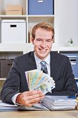 Smiling businesss man with Euro money fan sitting in his office